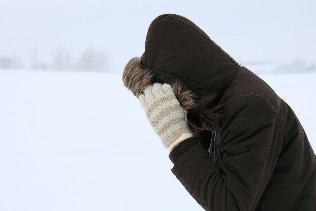 """Cubriéndose la cara de un """"blizard"""" o tormenta de nieve."""