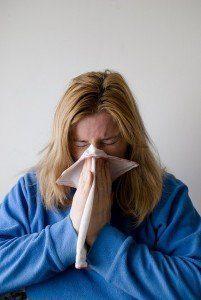 Mujer con pañuelo con un fuerte resfriado